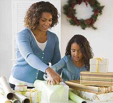 African mother and daughter wrapping gifts