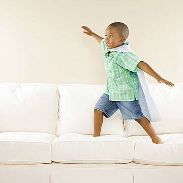 Young African boy playing on sofa