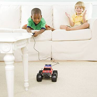 Two young boys playing with remote control car