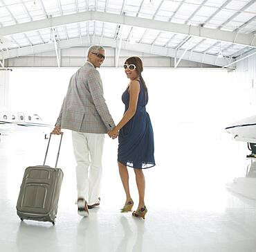 Couple walking out of airplane hanger