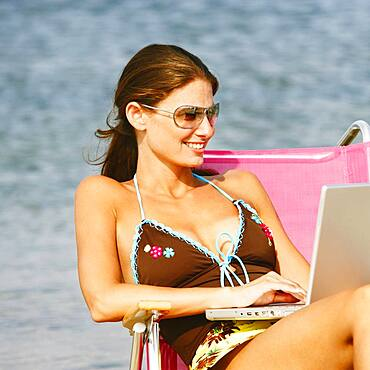 Woman typing on laptop at beach
