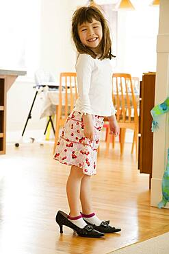 Young girl wearing mother's shoes