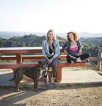 Caucasian women sitting with dog on hilltop
