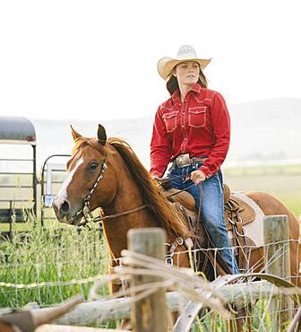 Caucasian cowgirl riding horse on ranch