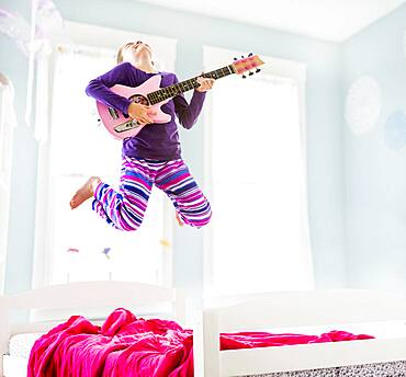 Caucasian girl playing guitar on bed