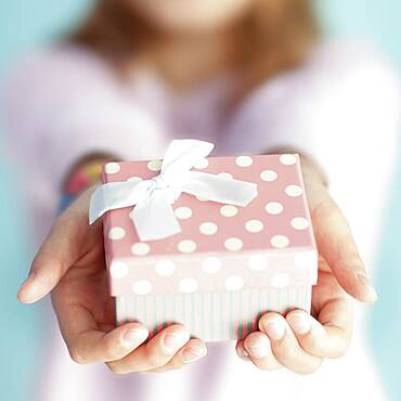 Close up of girl holding wrapped gift