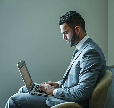 Businessman using laptop in armchair