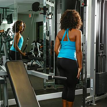 Woman using exercise machine in gymnasium