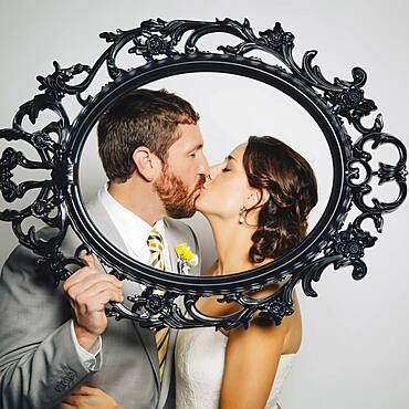 Caucasian bride and groom kissing behind empty frame