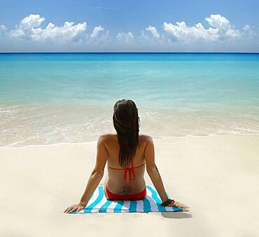 Caucasian woman laying on tropical beach