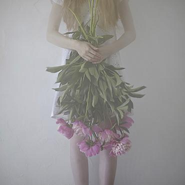 Caucasian teenage girl holding flowers upside-down