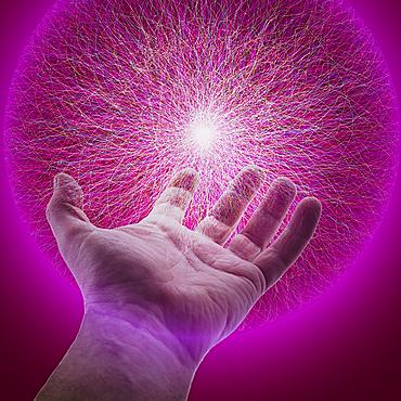Hand of Caucasian man holding glowing sphere of purple energy