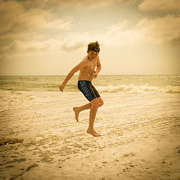 Caucasian boy jumping and splashing in ocean waves