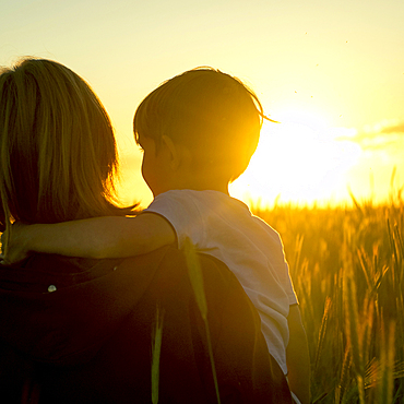 Mother carrying son in field of wheat at sunset