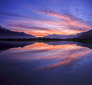 Panoramic view of Pian di Spagna flooded with snowy peaks reflected in the water at sunset, Valtellina, Lombardy, Italy, Europe