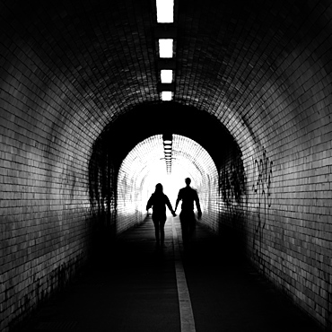 Couple walking into the light, York tunnel, York, England, United Kingdom, Europe
