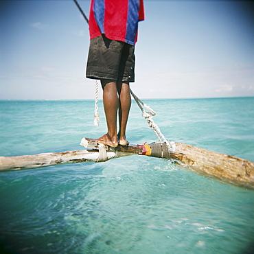 Man standing on outrigger in Indian Ocean, Zanzibar, Tanzania, East Africa, Africa