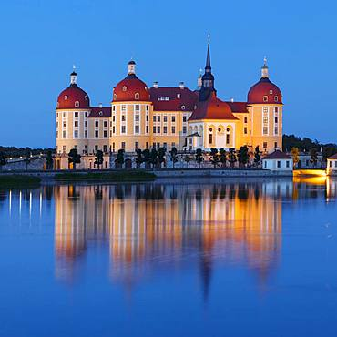 Illuminated Moritzburg Castle at dusk, water reflection in the lake, Saxony, Germany, Europe