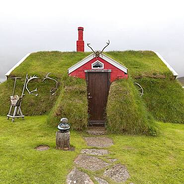 Traditional peat house Lindarbakki overgrown with grass and antlers in the red gable, Bakkageroi, Bakkagerdi, Borgarfjoerour, Borgarfjoerdur, Austurland, Iceland, Europe