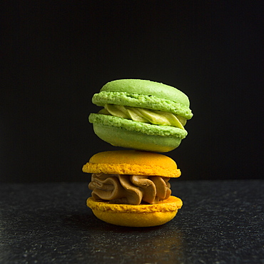 Two macarons on a black background