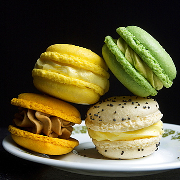 Four macarons on a black background