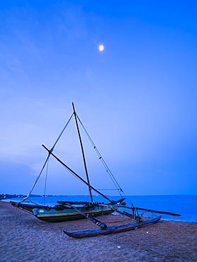 Traditional outrigger fishing boat (oruva) on Negombo Beach at night under the moon, Negombo, Sri Lanka, Asia
