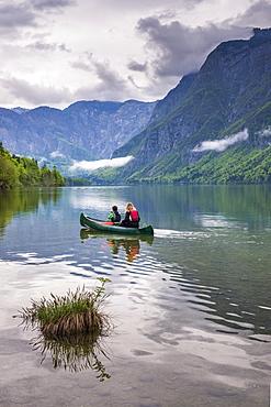 Mother and son canoeing on Lake Bohinj, Triglav National Park, Julian Alps, Slovenia, Europe