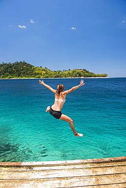 Woman jumping into the Pacific Ocean at Twin Beach, a tropical white sandy beach near Padang in West Sumatra, Indonesia, Southeast Asia, Asia