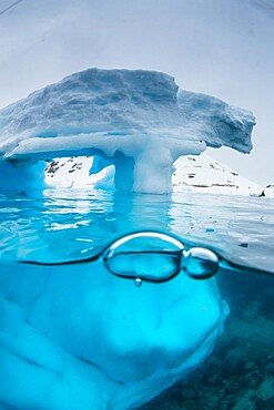 Above and below view of an arch formed in an iceberg at Cuverville Island, Ererra Channel, Antarctica, Polar Regions
