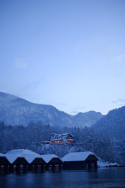 A hotel and snow covered huts at the lake shore, Königssee, Berchtesgardener Land, Bavaria, Germany