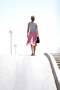 Woman walking on street, Portugal