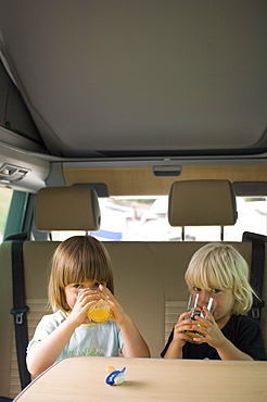 Two children sitting in a camper bus drinking orange juice, Bavaria, Germany
