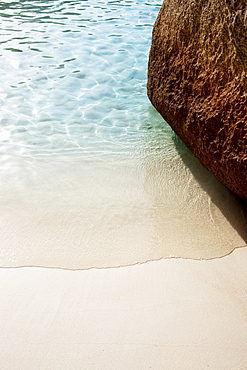 Wave washing around rock on fine white sandy beach, Similan Islands, Andaman Sea, Thailand