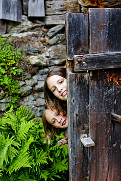 Two girls behind an old wooden door, Styria, Austria