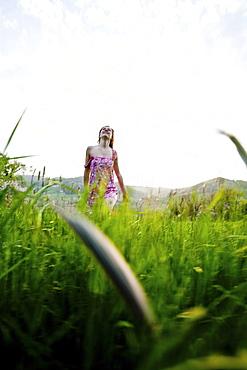 Young woman walking through high grass, Riegersburg, Styria, Austria