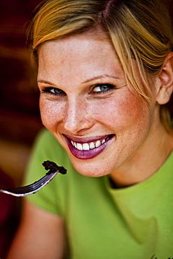 Young woman eating pancake with blueberries, lake Duisitzkar, Styria, Austria