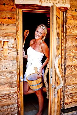 Young woman standing in door of a sauna, Fladnitz an der Teichalm, Styria, Austria