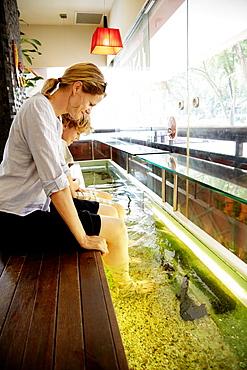 Woman and boy enjoying fish spa, Downtown Core, Singapore