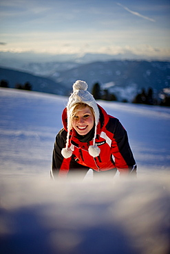 Young woman wearing a cap smiling at camera, Kreischberg, Murau, Styria, Austria