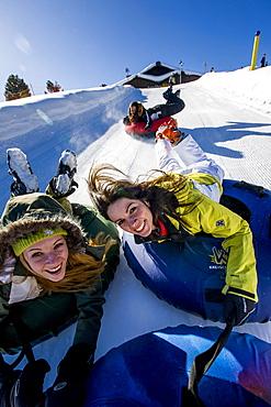 Young women snow tubing, Kreischberg, Murau, Styria, Austria