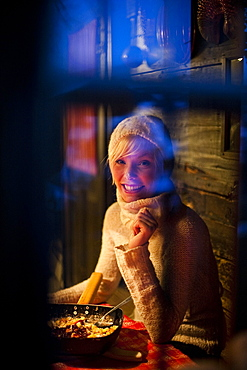 Smiling young woman looking through a window