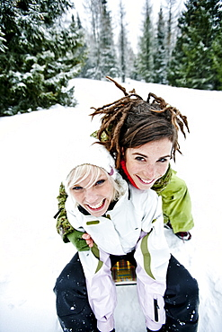 Two young women tobogganing