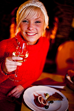 Young woman enjoying a glass of wine at dinner