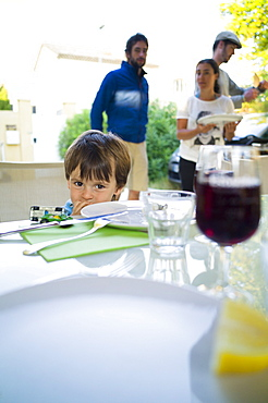 Boy sitting at a table, Perols, Montpellier, Herault, Languedoc-Roussillon, France