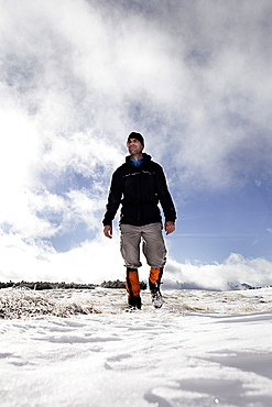 Hiker walking in snow-covered landscape, ascend to Unnutz Mountain (2078 m), Rofan Mountains, Tyrol, Austria