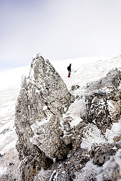 Hiker standing in snow-covered landscape, ascend to Unnutz Mountain (2078 m), Rofan Mountains, Tyrol, Austria
