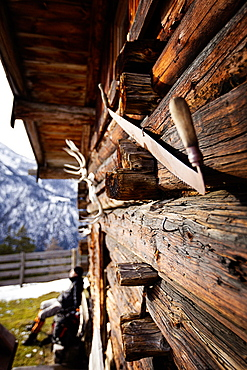 Wooden hut and hiker taking a rest, descent from Unnutz Mountain (2078 m), Rofan Mountains, Tyrol, Austria