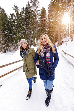 Two young women arm in arm walking in snow, Spitzingsee, Upper Bavaria, Germany