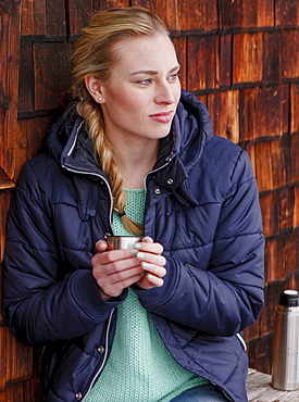 Young woman holding a mug, Spitzingsee, Upper Bavaria, Germany