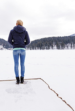 Young woman on a jetty at snow-covered lake Spitzingsee, Upper Bavaria, Germany